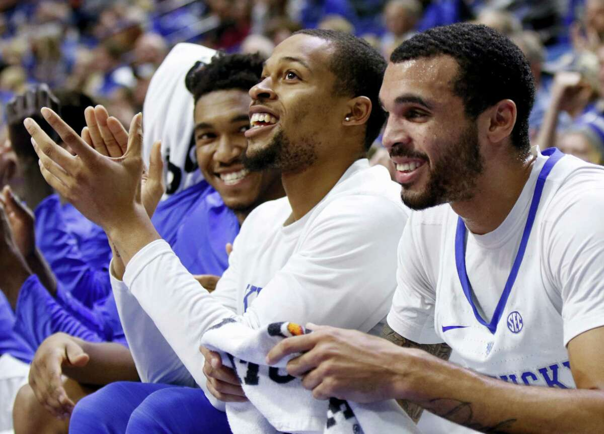 Kentucky's Isaiah Briscoe, middle, applauds a teammate between Malik Monk, left, and Mychal Mulder during a recent game.