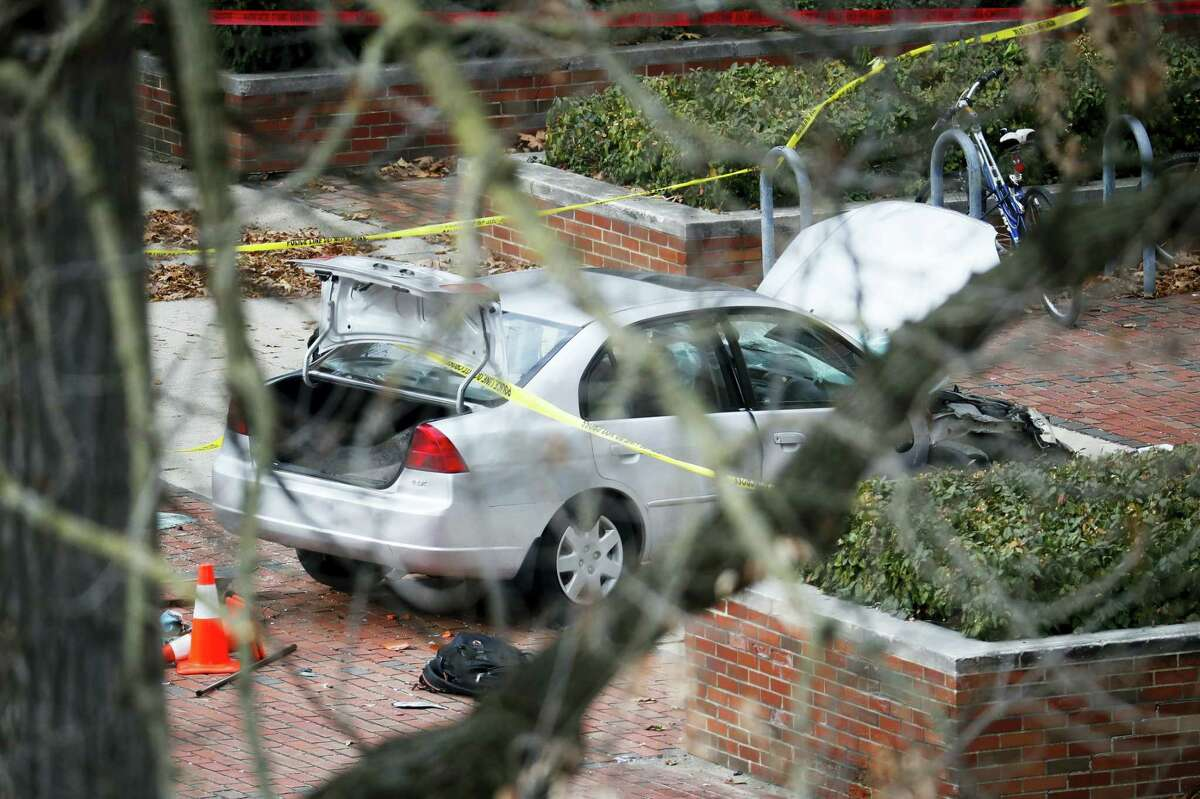 A car inside a police line sits on the sidewalk as authorities respond to an attack on campus at Ohio State University, Monday in Columbus, Ohio.