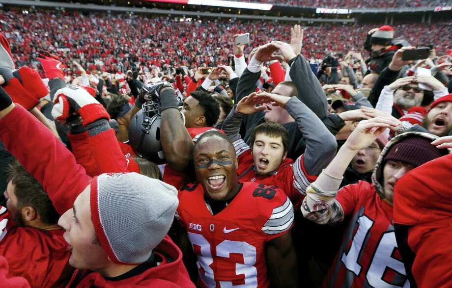 Ohio State players and fans celebrate their win over Michigan on Saturday. Photo: Jay LaPrete — The Associated Press   / FR52593 AP