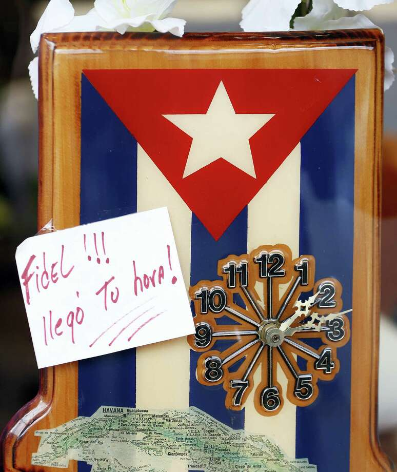 "A note reading ""Fidel!!! Your time has arrived"" is seen on a clock with the Cuban flag at Sugarman's Pharmacy in Union City, N.J., where a large concentration of people have Cuban ties, Saturday, Nov. 26, 2016. Business in a bustling shopping street are donning Cuban flags as news of Fidel Castro's passing began to spread. Photo: AP Photo/Julio Cortez    / Copyright 2016 The Associated Press. All rights reserved."