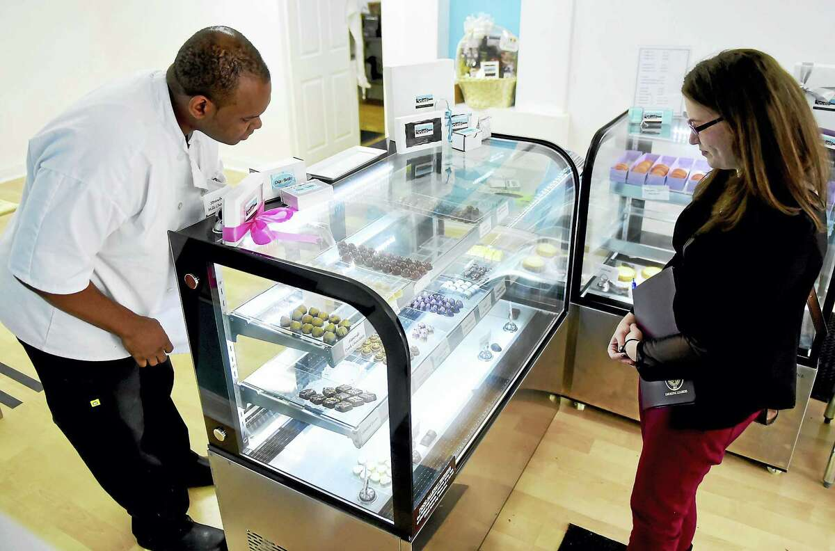 Darrell Nurse, owner and chocolatier of Chip In A Bottle specialty chocolate shop on Whalley Avenue in New Haven, serves customer Adrienne Griffith of Derby.