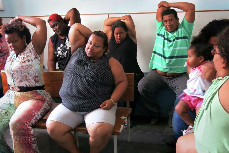 Elisângela Ferreira, 36, Luiz da Silva, 42, Lisyane Soares, 39, Cristiane do Nascimento, 34, Carlos Cordeiro, 50, Veronica Cabral, 28, (face hidden), her baby Lidia and daughter Debora, 8, take part in an exercise class for obese people at the nonprofit GRACO on Nov. 17. Photo: Photo By Dom Phillips For The Washington Post / Dom Phillips