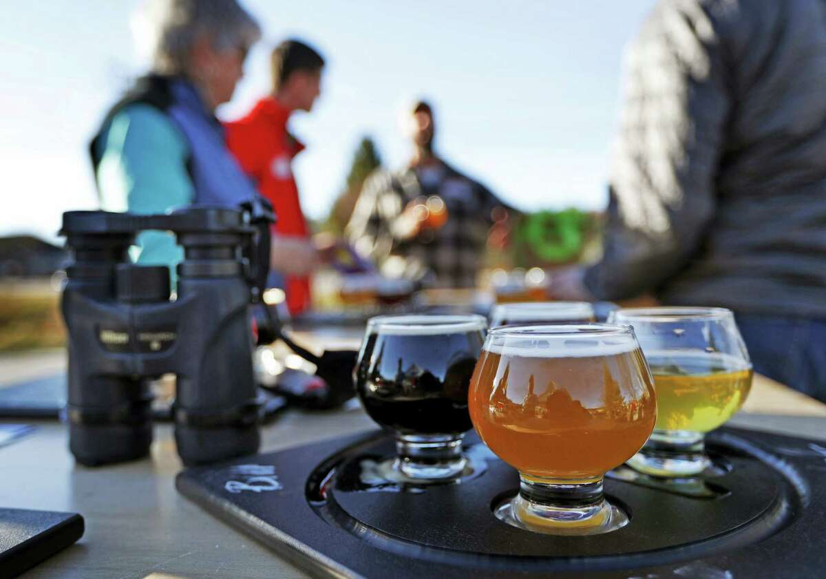 In this Sunday, Nov. 13, 2016 photo, a group of birding enthusiasts finish discuss their day while sampling a flight of beers at the Maine Brewing Company in Freeport, Maine. The Maine Brew Bus tour group combines bird watching and craft beers into popular trips throughout southern Maine.