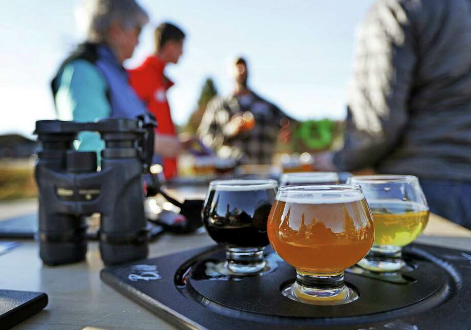 In this Sunday, Nov. 13, 2016 photo, a group of birding enthusiasts finish discuss their day while sampling a flight of beers at the Maine Brewing Company in Freeport, Maine. The Maine Brew Bus tour group combines bird watching and craft beers into popular trips throughout southern Maine. Photo: Robert F. Bukaty — AP Photo / Copyright 2016 The Associated Press. All rights reserved.