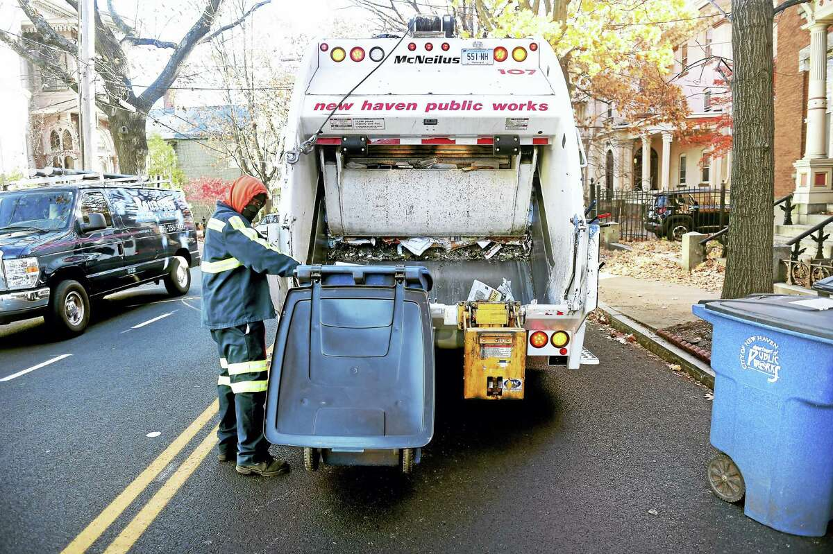 Thomas Dennie of the New Haven Public Works Department collects trash on Chapel Street in New Haven.