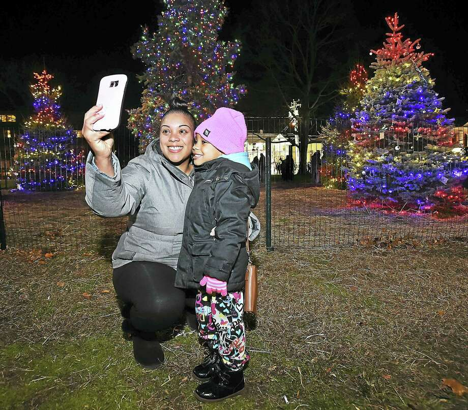 A West mother takes a selfie with her child following the annual lighting of the Christmas tree on the Green in West Haven Saturday. Photo: Catherine Avalone — New Haven Register / New Haven RegisterThe Middletown Press