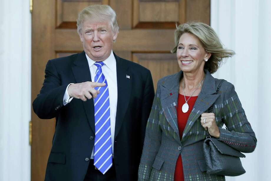 FILE - In this Nov. 19, 2016 file photo, President-elect Donald Trump and Betsy DeVos pose for photographs at Trump National Golf Club Bedminster clubhouse in Bedminster, N.J. Trump has chosen charter school advocate DeVos as Education Secretary in his administration. (AP Photo/Carolyn Kaster, File) Photo: AP / Copyright 2016 The Associated Press. All rights reserved.