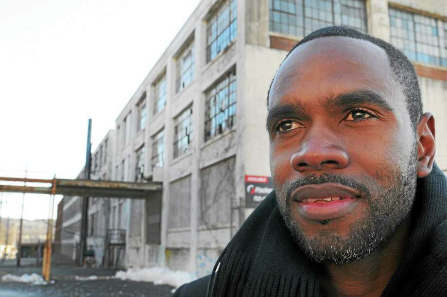 Developer Moustapha Diakhate , owner of Hamden, Conn. based Washington Management LLC , stands next to a Farrel Corp. property on East Main Street in Ansonia after being part of a press conference at Ansonia City Hall Thursday, January 24, 2013, announcing his company's purchase of the Farrel Complex for $1.9 million, making it one of the largest commercial real estate transactions in Ansonia in recent history.  January 24, 2013. Photo: Peter Hvizdak / New Haven Register / ©Peter Hvizdak /  New Haven Register