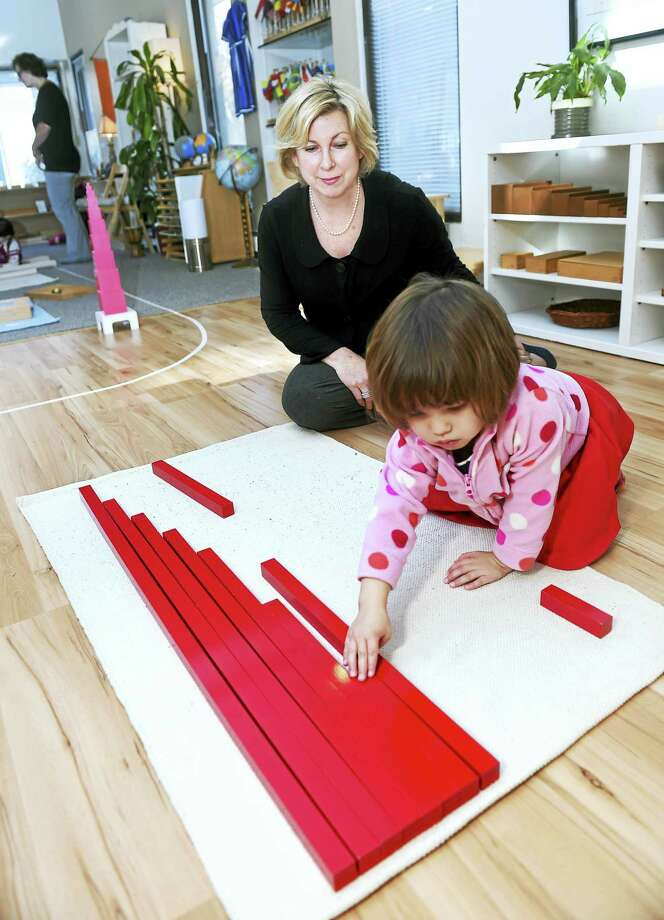 Rhonda Bielik (center), owner of Willow Tree Montessori, guides Jasmine Shavers, 3, with placing rods at the school in Bethany. Photo: Arnold Gold/new Haven Register