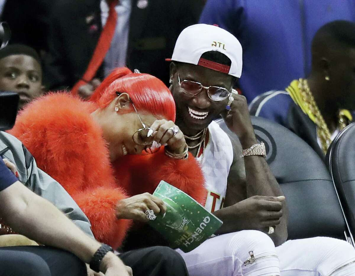 Hip Hop artist Gucci Mane, right, laughs with Keyshia Ka'oir after he proposed to her in the fourth quarter of an NBA basketball game between the Atlanta Hawks and the New Orleans Pelicans in Atlanta on Nov. 22, 2016.