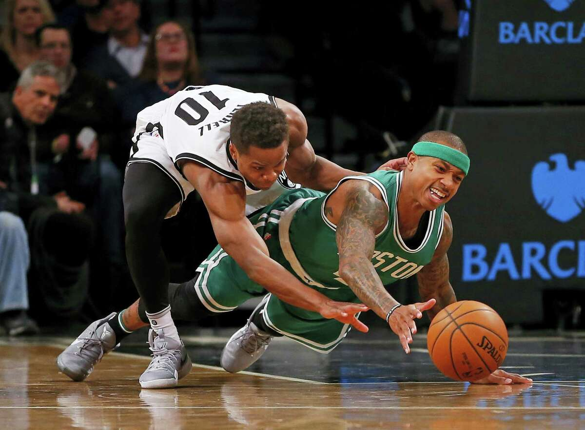 Brooklyn Nets guard Yogi Ferrell, left, and Boston Celtics guard Isaiah Thomas battle for the ball during the first half of an NBA basketball game in New York, Wednesday. The Celtics defeated the Nets 111-92.