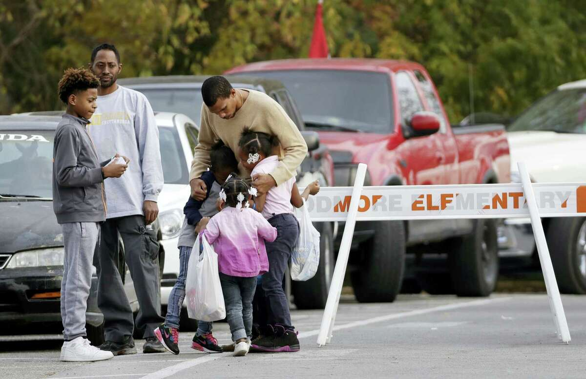 Children get a goodbye hug as students are picked up from Woodmore Elementary School on Tuesday, Nov. 22, 2016, in Chattanooga, Tenn. The school bus driven by Johnthony Walker, 24, crashed while transporting children home from the school Monday, killing at least five students. Walker was arrested Monday and charged with five counts of vehicular homicide including reckless driving and reckless endangerment, police said. (AP Photo/Mark Humphrey)
