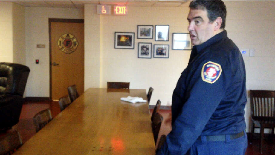 Branford firefighter paramedic Ralph Marino said firefighters eat Thanksgiving dinner at a wooden dining table made by a firefighter. Photo: Juliemar Ortiz — New Haven Register