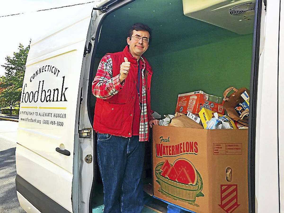 James Trimble helps load the food items he collected this year in addition to more than $3,000 in donations for the Connecticut Food Bank.