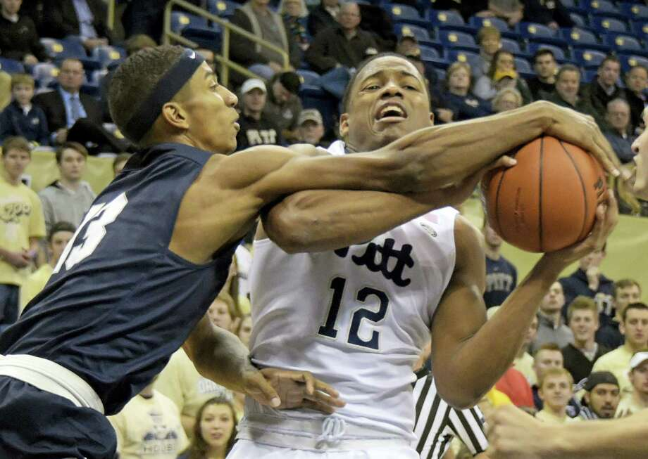 Yale guard Trey Phills (13) blocks a shot by Pittsburgh guard Chris Jones during the first half of Pitt's 75-70 win Tuesday in Pittsburgh. Photo: FRED VUICH - THE ASSOCIATED PRESS   / Fred Vuich