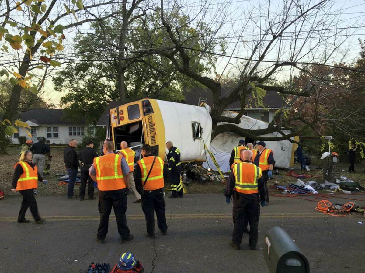In this photo provided by the Chattanooga Fire Department via Chattanooga Times Free Press, Chattanooga Fire Department personnel work the scene of a fatal elementary school bus crash in Chattanooga, Tenn., Monday, Nov. 21, 2016. In a news conference Monday, Assistant Chief Tracy Arnold said there were multiple fatalities in the crash.
