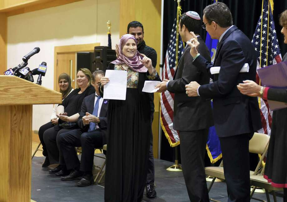 A refugee from Syria smiles after speaking as Gov. Dannel P. Malloy, second from right, gives an OK sign during a refugee celebration event at the Jewish Community Center of Greater New Haven, Tuesday, in Woodbridge. Malloy said Tuesday that he'll sue if the Trump Administration tries to withhold federal funds to New Haven and other so-called sanctuary cities that refuse to cooperate with federal immigration officials. Photo: Jon Olson/Hartford Courant Via AP / Hartford Courant