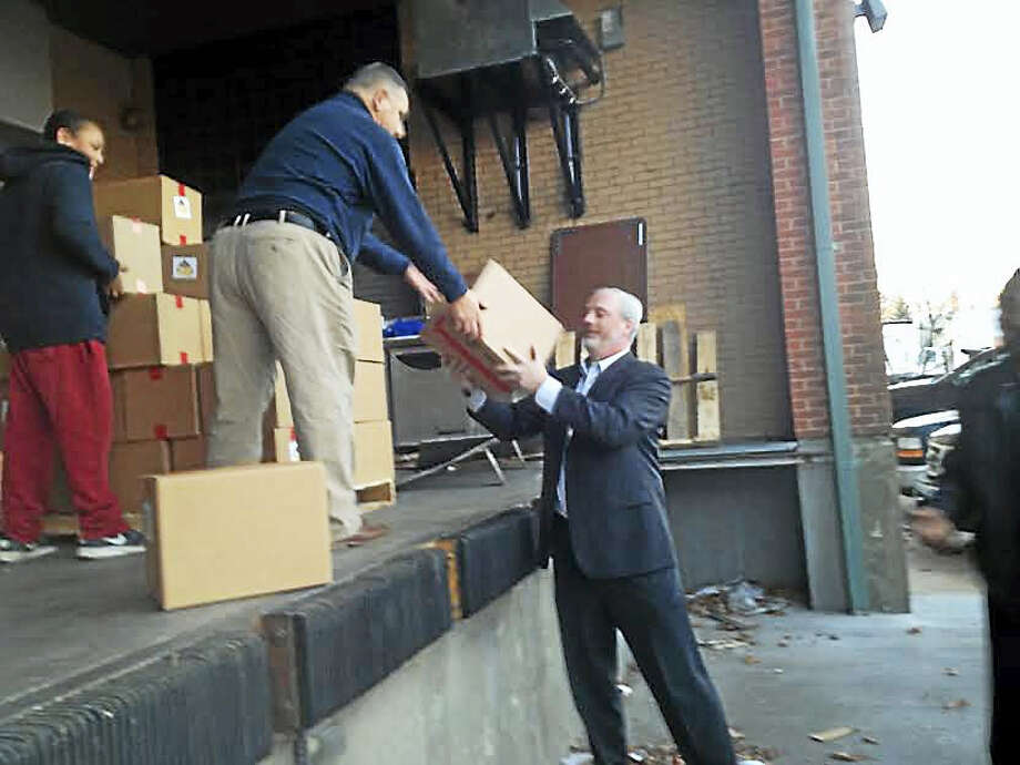 AFB Facilities Management President and CEO Al Barbarotta hands a package of food to New Haven Public Schools COO Will Clark. Photo: Brian Zahn — New Haven Register