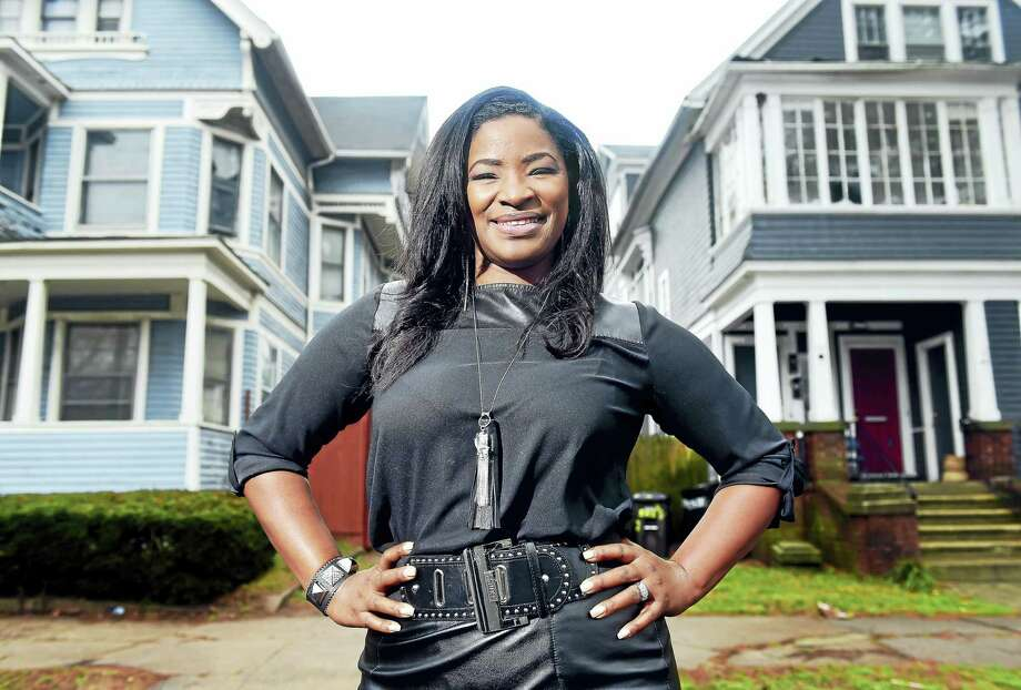 (Arnold Gold-New Haven Register)  Roberta Hoskie, President and CEO of Outreach Realty Services, is photographed in front of the first house she purchased at 283 Norton St. (left) in New Haven on 12/24/2015.  She no longer owns this home. Photo: Journal Register Co.