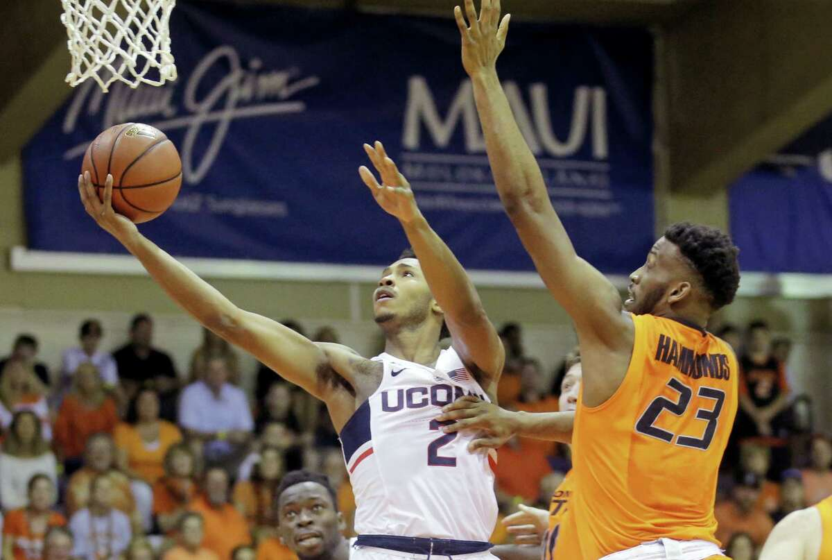 UConn's Jalen Adams, left, lays up the ball as Oklahoma State forward Leyton Hammonds defends on Monday.