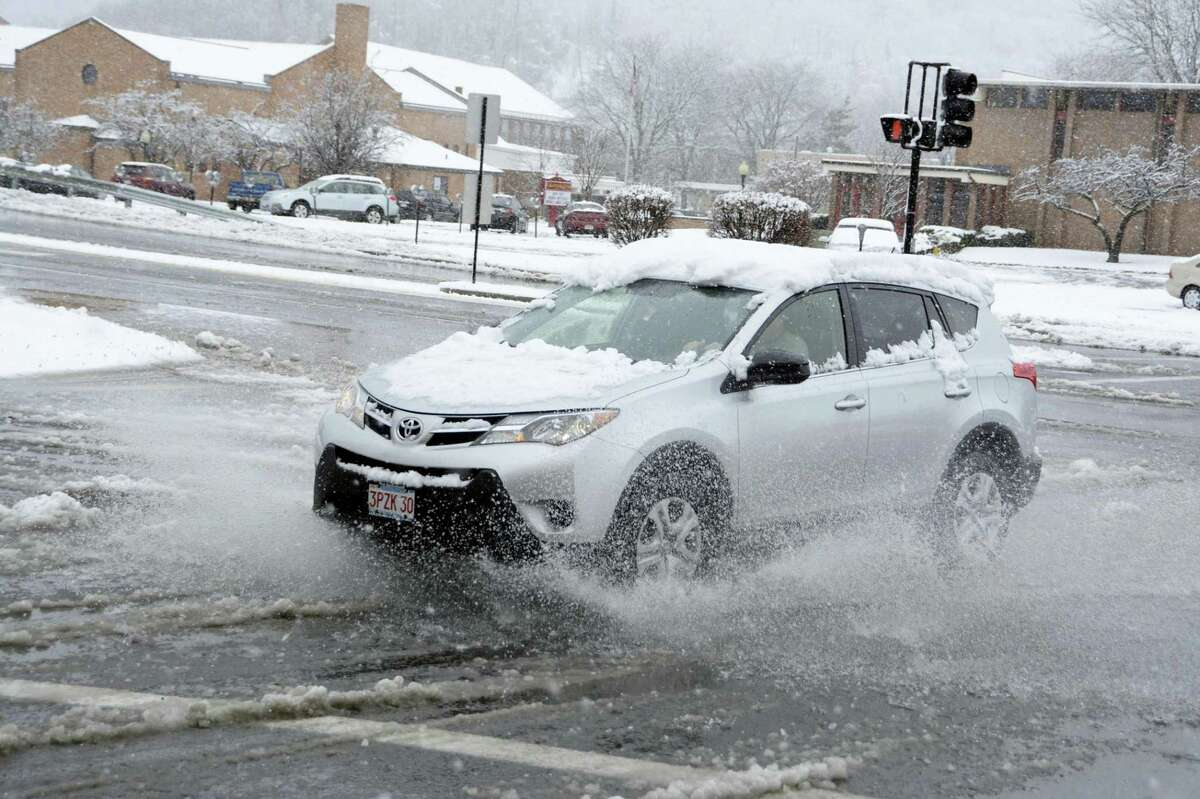 A car splashes through a slush puddle in North Adams, Mass., during a winter storm on Sunday, Nov. 20, 2016.