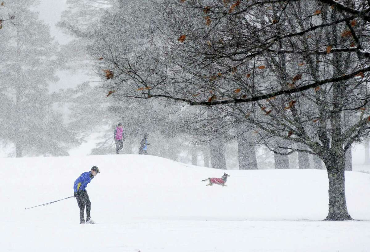 A cross country skier, a couple and a dog enjoy the snow at the Taconic Golf Club in Williamstown, Mass., during a winter storm on Sunday, Nov. 20, 2016.