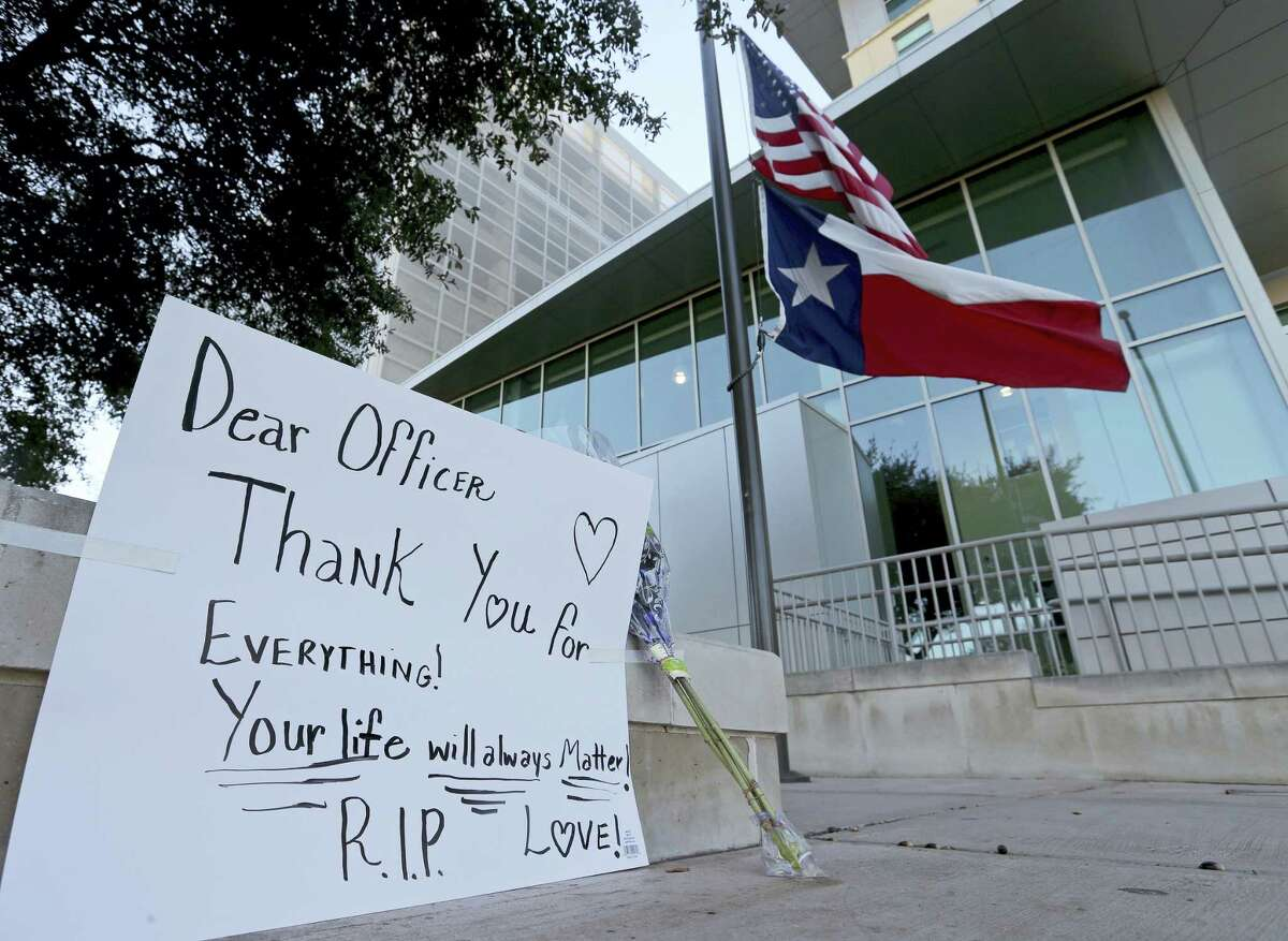 An American flag and a Texas state flag fly at half-staff at San Antonio Police Department headquarters near a sign and flowers left by Lucy Aldaba after Det. Benjamin Marconi was fatally shot Sunday, Nov. 20, 2016 in San Antonio. Marconi was writing out a traffic ticket to a motorist when he was shot to death in his squad car Sunday outside police headquarters by another driver who pulled up from behind, authorities said.