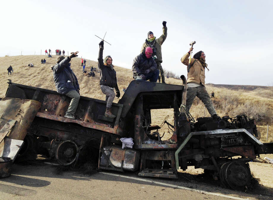 Protesters against the Dakota Access oil pipeline stand on a burned-out truck near Cannon Ball, N.D., Monday, Nov. 21, 2016, that they removed from a long-closed bridge on Sunday on a state highway near their camp in southern North Dakota. Opponents skirmished with law officers late Sunday and early Monday. (AP Photo/James MacPherson) Photo: AP / Copyright 2016 The Associated Press. All rights reserved.