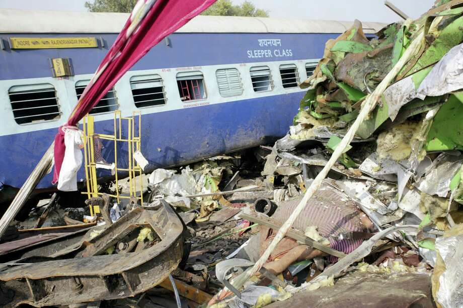 The body of a victim lies buried amid the mangled remains of crashed bogies after 14 coaches of an overnight passenger train rolled off the track near Pukhrayan village,Kanpur Dehat district, Uttar Pradesh state, India on Nov. 20, 2016. Dozens were killed and dozens more were injured in the accident. Photo: AP Photo/Rajesh Kumar Singh   / Copyright 2016 The Associated Press. All rights reserved.