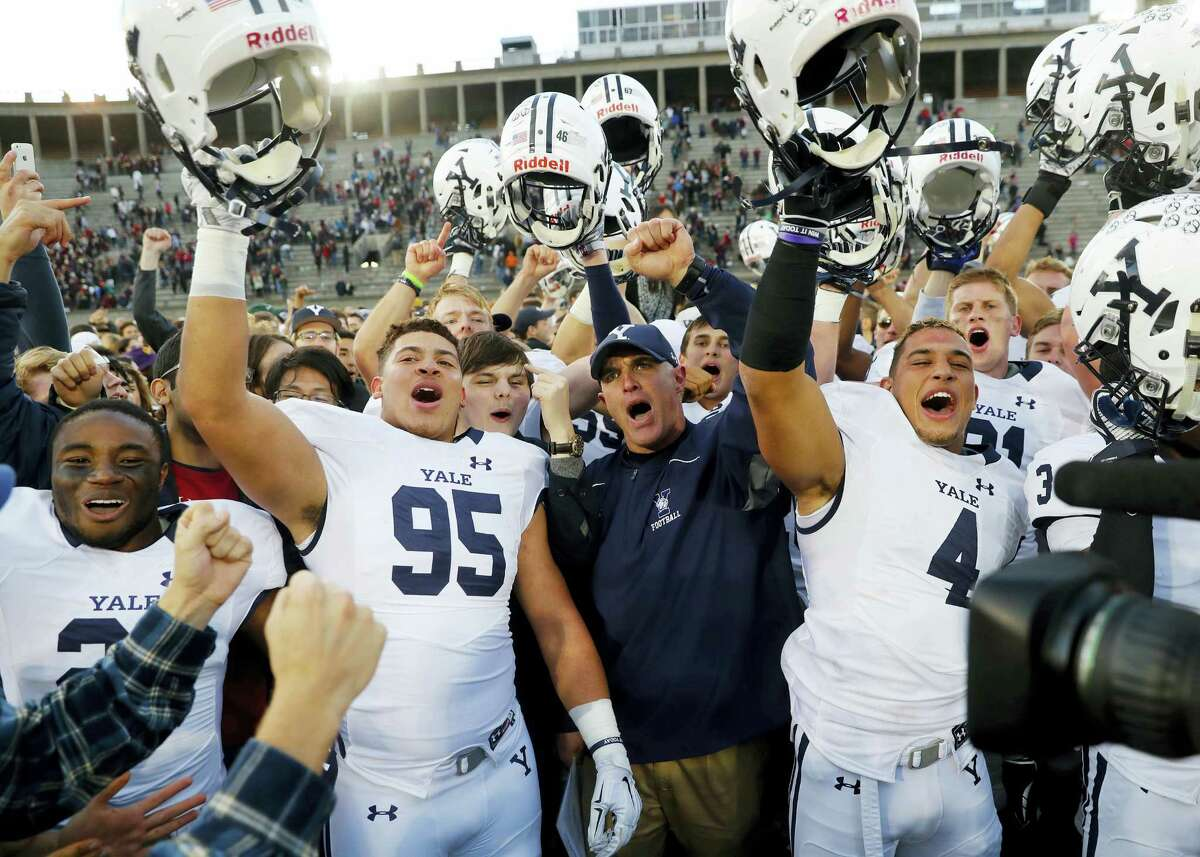 Yale head coach Tony Reno, center, celebrates with his team including Tim Dawson II (95) and Sebastian Little after their 21-14 win over Harvard Saturday in Cambridge, Mass.