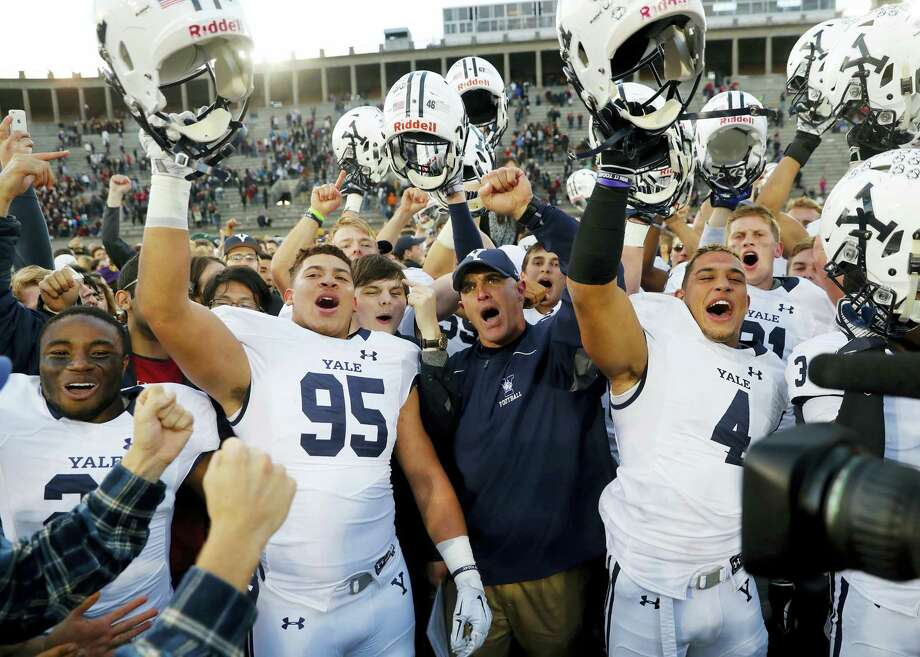 Yale head coach Tony Reno, center, celebrates with his team including Tim Dawson II (95) and Sebastian Little after their 21-14 win over Harvard Saturday in Cambridge, Mass. Photo: Winslow Townson — The Associated Press   / FR170221 AP