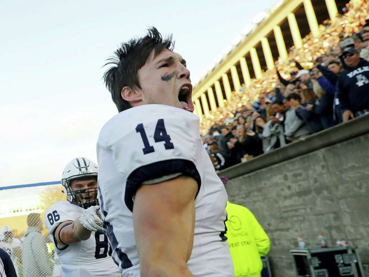 Yale wide receiver Reed Klubnik (14) celebrates with fans and teammate John Lager (86) after scoring the go-ahead touchdown during the second half.