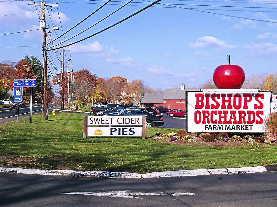 A blue sign indicating an electric vehicle charging station, left, is visible near the front entrance of Bishop's Orchards on the Boston Post Road in Guilford. That charging station will be part of an alternative fuels corridor along Interstate 95 in the New Haven area. Photo: Wes Duplantier —The New Haven Register