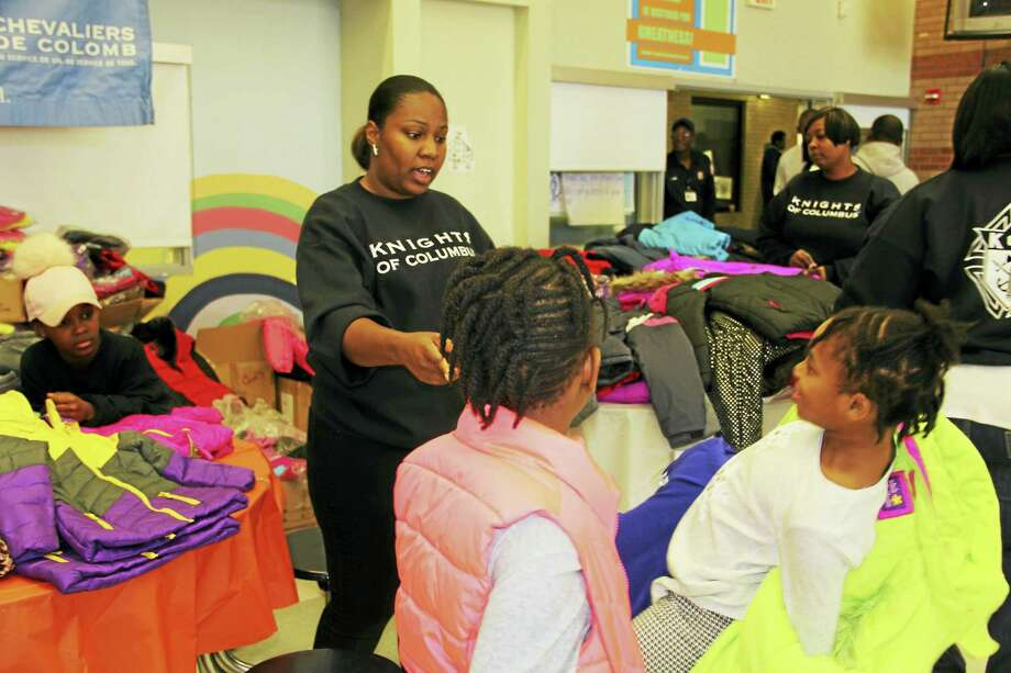 Quianna Richardson from the Knights of Columbus helps Kaliaya Frazier, 8, and her sister Azara try on coats at the third annual Day of Joy on Saturday. Photo: Anna Bisaro — New Haven Register