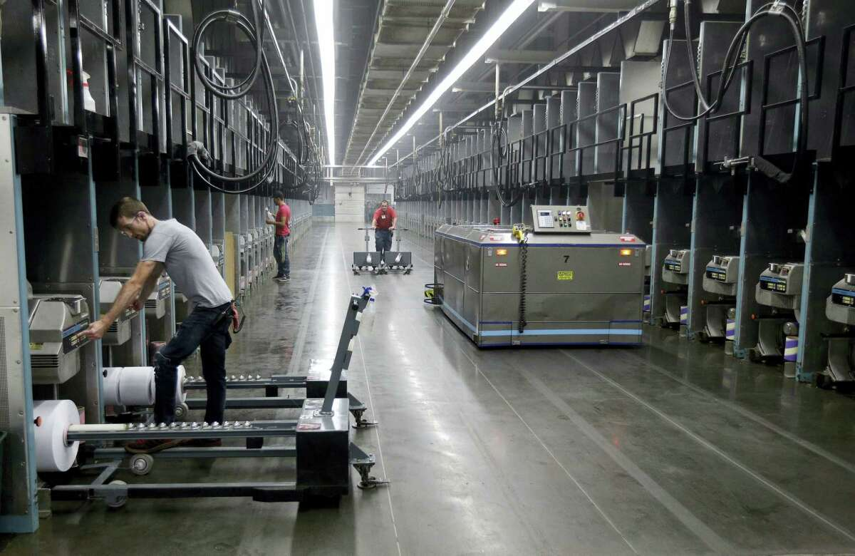 Workers exchange spools of thread as a robot picks up thread made from recycled plastic bottles at the Repreve Bottle Processing Center, part of the Unifi textile company, in Yadkinville, N.C.