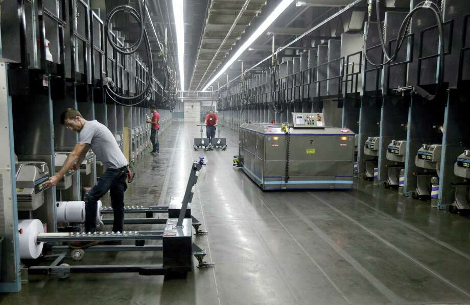 Workers exchange spools of thread as a robot picks up thread made from recycled plastic bottles at the Repreve Bottle Processing Center, part of the Unifi textile company, in Yadkinville, N.C. Photo: Chuck Burton — The Associated Press   / Copyright 2016 The Associated Press. All rights reserved.