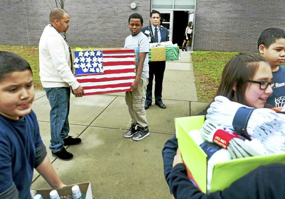 Larry Rice, rear left, and Benjamin Santiago, rear right, both of the Veterans Administration Connecticut Volunteer Services in West Haven, with John C. Daniels School fifth-grader Davon Hargrove, 10, center, wait for other fifth-graders in 2015 at the New Haven school to load up a car of donated personal items destined to for veterans who will be hospitalized over the Christmas holidays at the West Haven VA hospital. Photo: Peter Hvizdak - New Haven Register   / ©2015 Peter Hvizdak