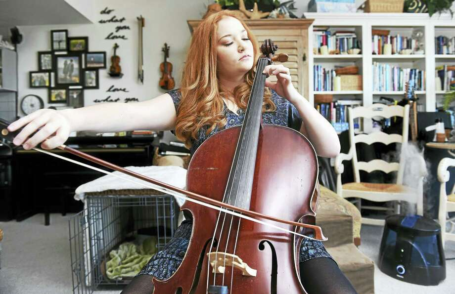 Sara Scanlon practices on her French cello, made by Rene Quenoil in 1950, at her home in Milford. Photo: Arnold Gold — New Haven Register