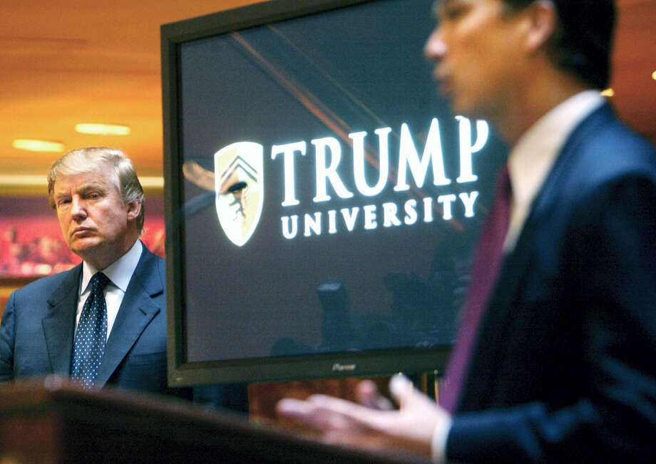 """Then real estate mogul and Reality TV star Donald Trump, left, listens as Michael Sexton introduces him at a news conference in New York where he announced the establishment of Trump University in 2005. A federal judge in San Diego will consider arguments on President-elect Trump's latest request to delay a civil fraud trial involving his now-defunct Trump University until after his inauguration on Jan. 20, 2017. Trump's attorneys said in a court filing ahead of the hearing, Friday, Nov. 18, 2016, that preparations for the White House were """"critical and all-consuming."""" Photo:  Bebeto Matthews — AP File Photo / Copyright 2016 The Associated Press. All rights reserved."""