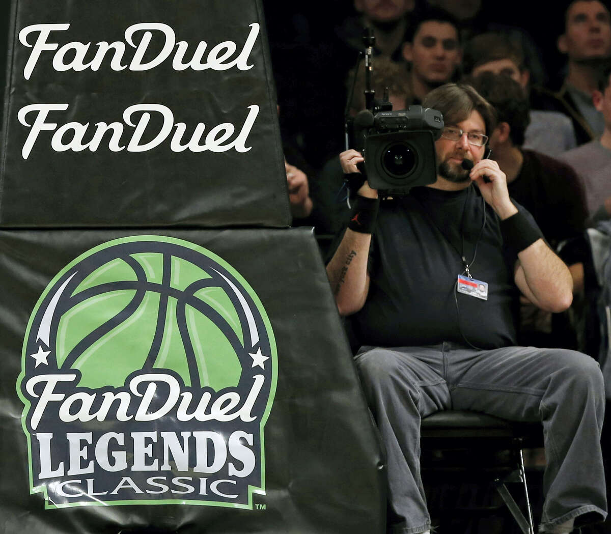 FILE - In this Nov. 24, 2015 file photo, FanDuel advertising covers the post at an NCAA college basketball matchup in the FanDuel Legends Classic consolation game, at the Barclays Center in New York. Daily fantasy sports rivals DraftKings and FanDuel have agreed to merge after months of speculation and increasing regulatory scrutiny. The two companies made the announcement Friday, Nov. 18, 2016, saying the combined organization would be able to reduce costs as they work to become profitable and battle with regulators across the country to remain legal.