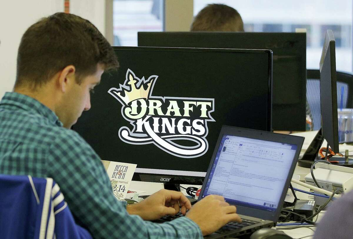 FILE - In this Sept. 9, 2015, file photo, Bear Duker, a marketing manager for strategic partnerships at DraftKings, works at his computer at the company headquarters in Boston. Daily fantasy sports rivals DraftKings and FanDuel have agreed to merge after months of speculation and increasing regulatory scrutiny. The two companies made the announcement Friday, Nov. 18, 2016, saying the combined organization would be able to reduce costs as they work to become profitable and battle with regulators across the country to remain legal.