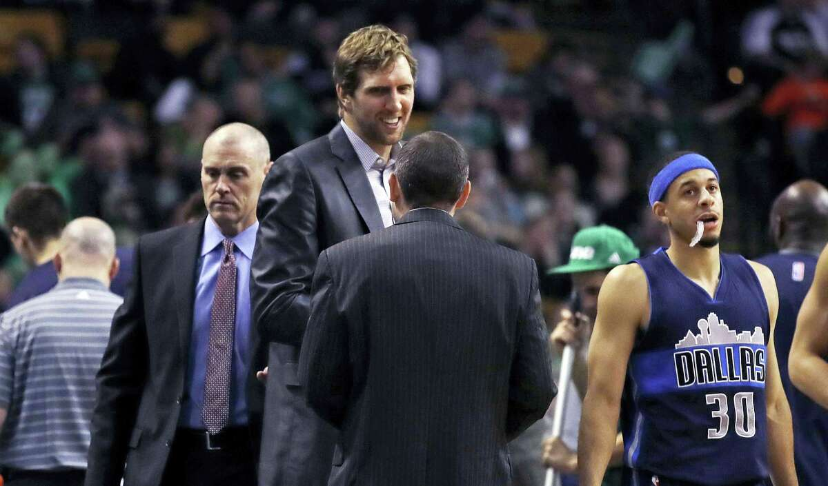 Dallas Mavericks forward Dirk Nowitzki, center, talks with a coach during a timeout in the second half of the team's NBA basketball game against the Boston Celtcis in Boston on Wednesday, Nov. 16, 2016. The Celtics defeated the Mavericks 90-83.
