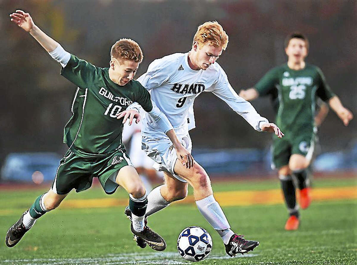 Daniel Hand senior Jake Brown battles Guilford senior Alex Gannon in a 3-0 win for the Tigers, in the CIAC class L soccer semifinals Wednesday.