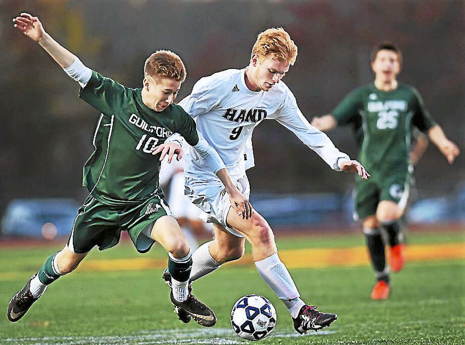 Daniel Hand senior Jake Brown battles Guilford senior Alex Gannon in a 3-0 win for the Tigers, in the CIAC class L soccer semifinals Wednesday. Photo: Catherine Avalone — New Haven Register