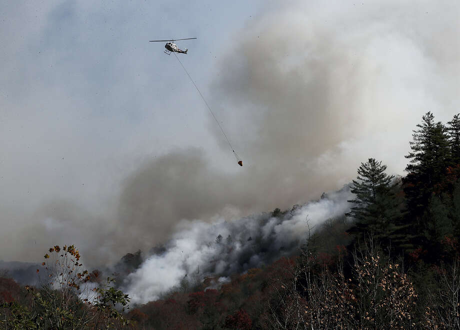 A helicopter works dropping water on the Rock Mountain wildfire as it approaches homes, Wednesday, Nov. 16, 2016, in Tate City, Ga. Photo: Curtis Compton/Atlanta Journal-Constitution Via AP    / Atlanta Journal-Constitution