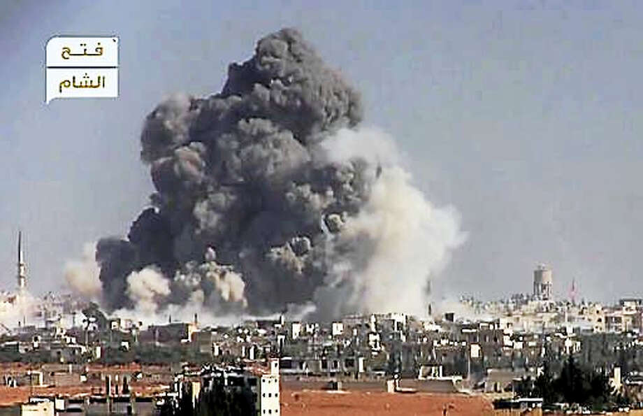 This frame grab from video provided by this militant video by Fatah al-Sham Front that is consistent with independent AP reporting, shows black smoke rises from a suicide bomb attacked Syrian government forces positions, in western Aleppo, Syria, Thursday, Nov. 3, 2016. The Britain-based Syrian Observatory for Human Rights, which monitors the conflict through local contacts, reported that rebels attacked government positions with two explosives-laden vehicles. Syrian rebels launched a fresh wave of attacks on western districts of Aleppo Thursday as airstrikes on a rebel-held village south of the contested city killed civilians, activists said. Photo: Militant Video By Fatah Al-Sham Front, Via AP    / Militant video by Fatah al-Sham