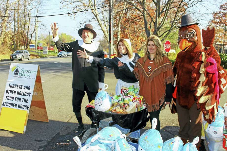 Dr. Bruce Sofferman, with his wife, Deborah, and daughter, Sophia, along with Spooner House employee Brian Gomez as a turkey, collect food at their annual drive. Photo: Jean Falbo-Sosnovich — New Haven Register