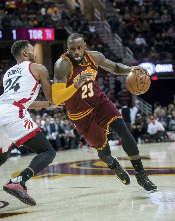 Cleveland Cavaliers' LeBron James (23) drives past Toronto Raptors' Norman Powell (24) during the first half of an NBA basketball game in Cleveland Tuesday, Nov. 15, 2016. Photo: AP Photo/Phil Long   / FR53611 AP