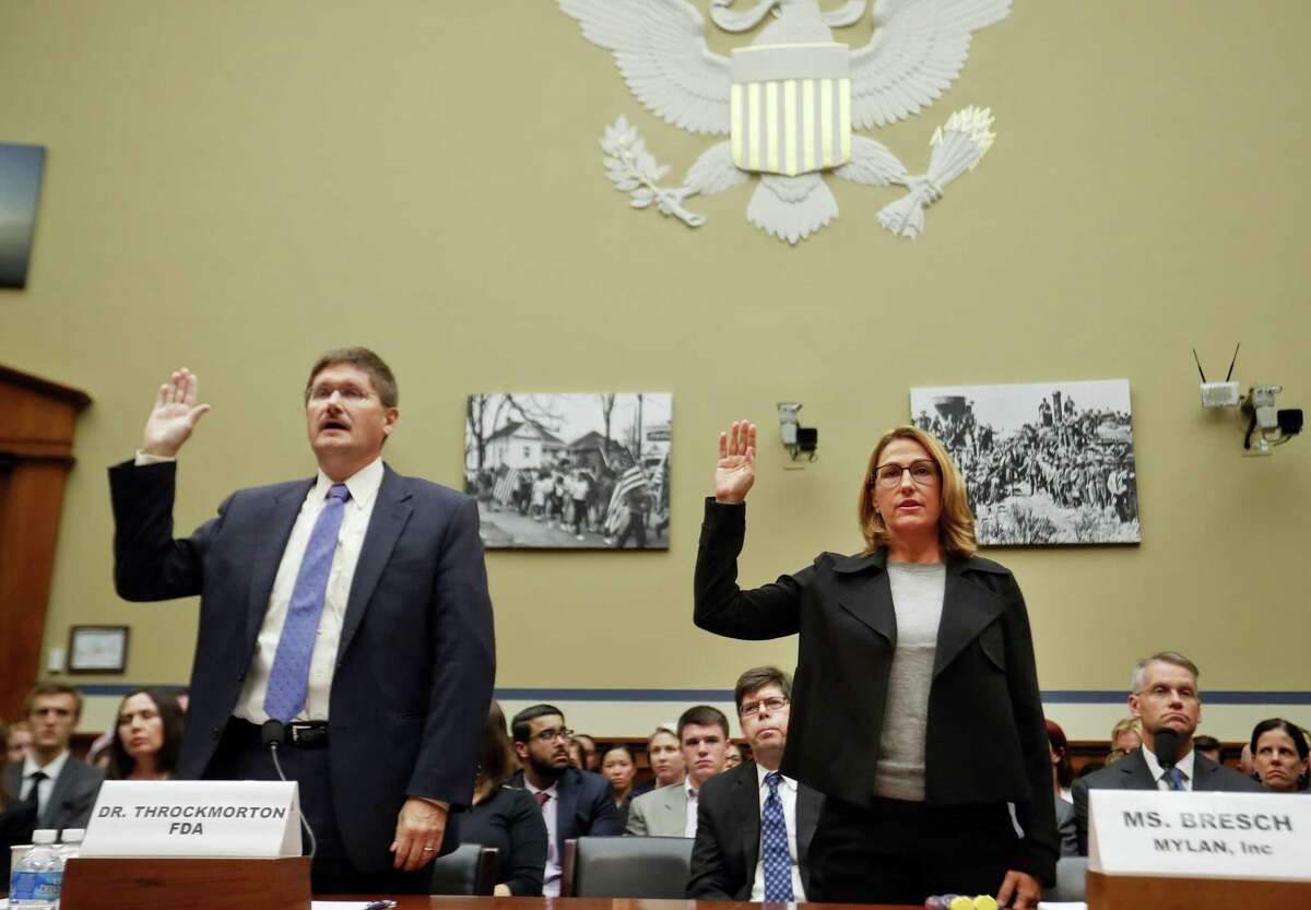 In this Sept. 21, 2016 photo, Mylan CEO Heather Bresch, right, and Dr. Doug Throckmorton, deputy director, Center for Drug Evaluation and Research, Food and Drug Administration (FDA), are sworn in on Capitol Hill in Washington, prior to testifying before the House Oversight Committee hearing on EpiPen price increases. Bresch defended the cost for life-saving EpiPens, signaling the company has no plans to lower prices despite a public outcry and questions from skeptical lawmakers.
