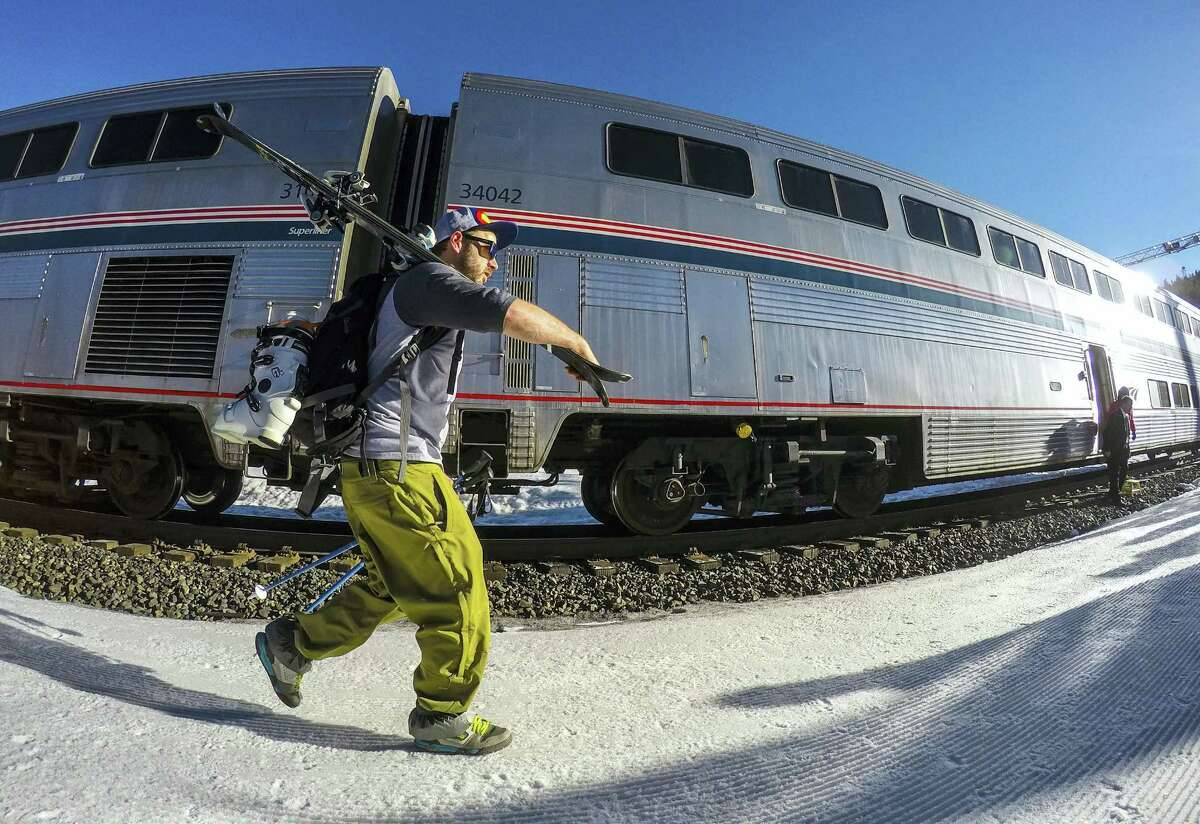A skier heads for his seat on the Winter Park ski train as it waits to leave from Winter Park, Colo., for Denver's Union Station. The historic train for skiers is resuming service from Denver's Union Station to the Rocky Mountains through 29 tunnels.